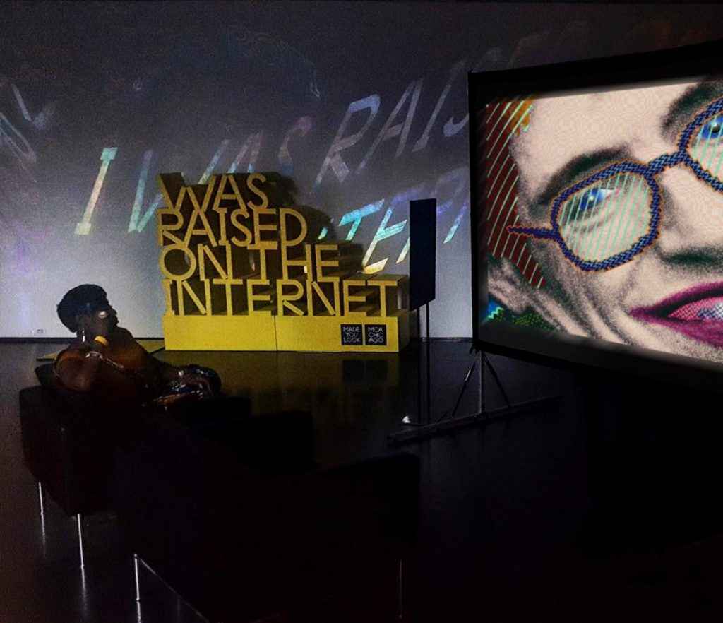 a woman sits on a couch at the Museum of Contemporary Art in Chicago, watching an animation of Stephen Hawking. In the background is a yellow sculpture forming the words I WAS RAISED ON THE INTERNET